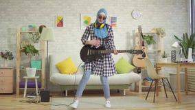 Η εύθυμη μουσουλμανική νέα γυναίκα στο hijab παίζει την ηλεκτρο κιθάρα στο σπίτι απόθεμα βίντεο