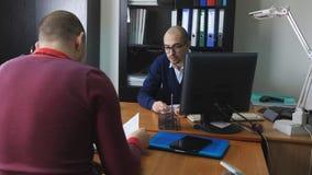Η εστίαση ραφιών στο άτομο από το τμήμα του ανθρώπινου δυναμικού παίρνει συνέντευξη από έναν πιθανό υπάλληλο στο γραφείο φιλμ μικρού μήκους