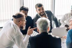 Η εταιρική διαφυλετική επιχειρησιακή ομάδα με τον εύθυμο ηγέτη σε μια συνεδρίαση, κλείνει επάνω στοκ φωτογραφίες με δικαίωμα ελεύθερης χρήσης