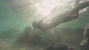Η ευτυχής γυναίκα στα προστατευτικά δίοπτρα για υποβρύχιο κολυμπά την κολύμβηση με αναπνευστήρα στην μπλε θάλασσα στο υπόβαθρο ηλ απόθεμα βίντεο