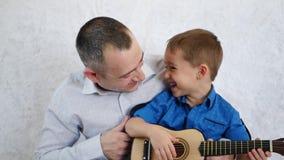 Η ευτυχής κιθάρα παιχνιδιού πατέρων και γιων, τραγουδά και γελά φιλμ μικρού μήκους