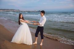 Η ευτυχής λαβή ζευγών αγάπης newlyweds κάθε άλλοι δίνει στην ωκεάνια παραλία Όμορφοι νύφη και νεόνυμφος στη ημέρα γάμου υπαίθρια στοκ φωτογραφία με δικαίωμα ελεύθερης χρήσης