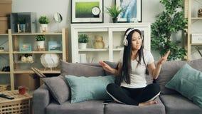 Η ευτυχής νέα κυρία στον περιστασιακό ιματισμό ακούει τη μουσική με τα ακουστικά, το χορό και τη συνεδρίαση τραγουδιού στον καναπ απόθεμα βίντεο