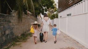 Η ευτυχής νέα μητέρα περπατά μαζί με δύο μικρά παιδιά που φέρνουν τις τσάντες αγορών προς το σπίτι κατά μήκος λίγης στενής αλέας φιλμ μικρού μήκους