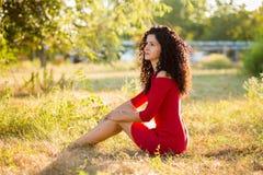 Η ευτυχής όμορφη νέα γυναίκα στο κόκκινο φόρεμα χαλαρώνει στο θερινό πάρκο μαύρη ελευθερία έννοιας που απομονώνεται στοκ φωτογραφία με δικαίωμα ελεύθερης χρήσης