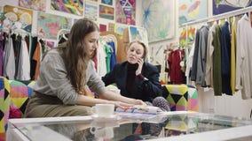 Η επιχειρηματίας μιλά πέρα από το smartphone ενώ άλλη νέα γυναίκα που διαβάζει το περιοδικό φιλμ μικρού μήκους