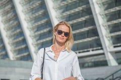 Η επιχειρησιακή γυναίκα σε ένα άσπρο πουκάμισο διέσχισε τα όπλα της πέρα από το στήθος ενάντια σύγχρονου κτηρίου της στοκ εικόνες