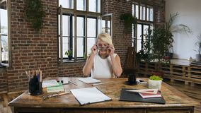 Η επιχειρησιακή κυρία κάθεται στον πίνακα που φορά τα γυαλιά που λειτουργούν αναπτυσσόμενος ένα νέο πρόγραμμα και καταγράφοντας κ απόθεμα βίντεο