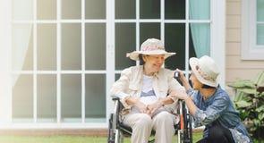 Η ηλικιωμένη γυναίκα χαλαρώνει στο κατώφλι με την κόρη στοκ εικόνες