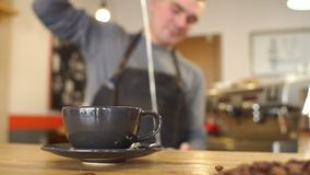 Η θολωμένη εικόνα ενός ατόμου που χύνει το γάλα σε ένα φλυτζάνι, στο πρώτο πλάνο είναι ένα φλυτζάνι απόθεμα βίντεο