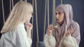 Η θρησκευτική μουσουλμανική γυναίκα και ο θηλυκός κοσμικός ξανθός φίλος της μιλούν φιλικό απόθεμα βίντεο