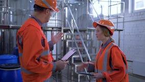 Η ισότητα φίλων στο εργοστάσιο, ευτυχής άνδρας με τους μηχανικούς γυναικών στα σκληρά καπέλα τινάζει τα χέρια και συζητά το νέο π απόθεμα βίντεο