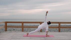 Η ισχυρή γυναίκα κάνει τις θέσεις γιόγκας, κλίνοντας τα χέρια στο πάτωμα, seacoast πίσω απόθεμα βίντεο