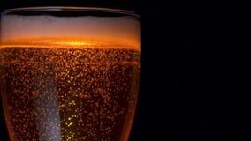 Η κινηματογράφηση σε πρώτο πλάνο που αυξάνεται επάνω σε πολλές χρυσές φυσαλίδες αέρα της δροσισμένης μπύρας στο μεγάλο γυαλί με τ φιλμ μικρού μήκους