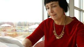 Η κομψή ηλικίας γυναίκα, καυκάσιο έθνος, διαβάζει τις επιλογές απόθεμα βίντεο
