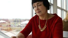 Η κομψή ηλικίας γυναίκα, καυκάσιο έθνος, διαβάζει τις επιλογές στο εστιατόριο ή τον καφέ φιλμ μικρού μήκους