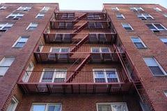 Η κόκκινη έξοδος κινδύνου υποστηρίζει σκαλοπάτι-κεντρικός τον αρχιτεκτονική-χάλυβα αλεών και το τούβλινο υπόβαθρο στοκ εικόνες