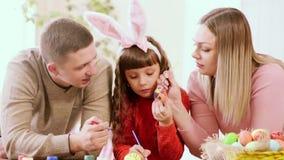 Η κόρη κρατά ένα αυγό κοτόπουλου, και οι γονείς της το διακοσμούν απόθεμα βίντεο