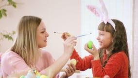 Η κόρη με το mom διακοσμεί τα αυγά κοτόπουλου, και έπειτα τις ο ένας του άλλου μύτες γαργαλήματος με τις βούρτσες γελούν σκληρά απόθεμα βίντεο
