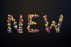 Η λέξη νέα γράφεται στον παχύ τύπο αστεριών ζύμης ζάχαρης σε ένα μαύρο υπόβαθρο, για, διαφήμιση, εμπόριο, πωλήσεις στοκ φωτογραφία