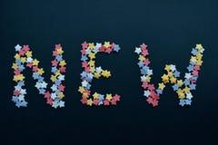 Η λέξη νέα στα κόκκινα άσπρα κίτρινα και μπλε αστέρια ζάχαρης, για την επιχείρηση, διαφήμιση, εμπόριο, πωλήσεις στοκ εικόνες