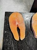 Η λωρίδα σολομών τεμαχίζει ένα φρέσκο πορτοκαλί χρώμα, σε έναν ξύλινο τεμαχίζοντας πίνακα για το μαγείρεμα Μέσα στην κουζίνα στοκ φωτογραφία με δικαίωμα ελεύθερης χρήσης