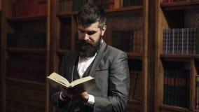 Η μελέτη, μαθαίνει, εκπαίδευση, έρευνα, ιστορία, έννοια λογοτεχνίας Ο σπουδαστής στέκεται στην εκλεκτής ποιότητας βιβλιοθήκη και  φιλμ μικρού μήκους