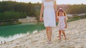 Η μητέρα και η κόρη που περπατούν στην παραλία στην όμορφη λίμνη με το κυανό νερό, η μητέρα μου είναι ο βραχίονας ενός κοριτσιού φιλμ μικρού μήκους