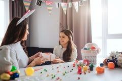 Η μητέρα και η κόρη προετοιμάζονται για Πάσχα στο καλό δωμάτιο Κρατούν παρών από κοινού Η νέα γυναίκα και το κορίτσι εξετάζουν κά στοκ εικόνες με δικαίωμα ελεύθερης χρήσης