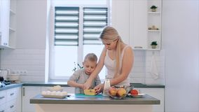 Η μητέρα διδάσκει το γιο για να τεμαχίσει το τυρί Μια νέα όμορφη μητέρα με στο λευκό πουκάμισο και το χαριτωμένο μάγειρα γιων σε  απόθεμα βίντεο