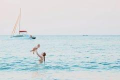 Η μητέρα ρίχνει επάνω στο μωρό στον ουρανό στο νερό της θάλασσας Ευτυχής ελεύθερος χρόνος οικογενειακού καλοκαιριού με το κορίτσι στοκ φωτογραφίες
