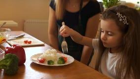 Η μητέρα ταΐζει στην κόρη της ένα υγιές μεσημεριανό γεύμα στην κουζίνα Το παιδί μασά τις ντομάτες κερασιών, η μητέρα είναι ευτυχή φιλμ μικρού μήκους