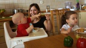 Η μητέρα ταΐζει τη συνεδρίαση μωρών στο highchair Το παιδί δεν θέλει να φάει και αρπάζει ένα κουτάλι με το χέρι του μητέρες φιλμ μικρού μήκους