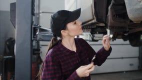 Η μηχανική, πανέμορφη εμφάνιση κορίτσι-αυτοκινήτων, brunette, συμμετέχει στην επισκευή του αυτοκινήτου στο πρατήριο βενζίνης φιλμ μικρού μήκους