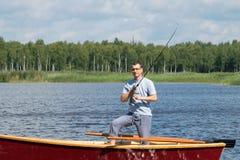 Η μπροστινή άποψη, ένα άτομο που στέκεται σε μια βάρκα στον ποταμό αλιεύει για την περιστροφή στοκ φωτογραφία με δικαίωμα ελεύθερης χρήσης