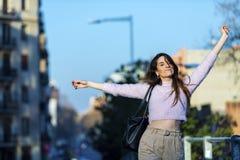 Η μπροστινή άποψη της χαμογελώντας όμορφης νέας γυναίκας οπλίζει αυξημένος και στεμένος στην οδό κάμερα σε μια ηλιόλουστη ημέρα στοκ φωτογραφίες