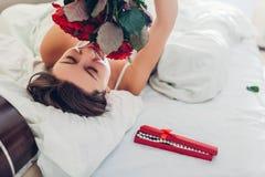 Η νέα γυναίκα βρήκε την ανθοδέσμη των τριαντάφυλλων με τα κοσμήματα στο κιβώτιο δώρων στο κρεβάτι Ευτυχή μυρίζοντας λουλούδια κορ στοκ εικόνες