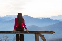 Η νέα γυναίκα κάθεται στον πάγκο εξωτερικό και εξετάζει το εικονογραφικό τοπίο με τα βουνά στοκ εικόνες με δικαίωμα ελεύθερης χρήσης