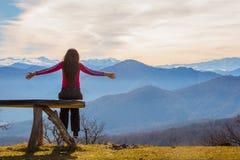 Η νέα γυναίκα κάθεται στον πάγκο εξωτερικό και εξετάζει το εικονογραφικό τοπίο με τα βουνά στοκ φωτογραφίες
