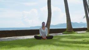 Η νέα γυναίκα κάνει την πρακτική γιόγκας, τέντωμα, που χαλαρώνει στην παραλία, το όμορφους υπόβαθρο και τους ήχους φύσης φιλμ μικρού μήκους