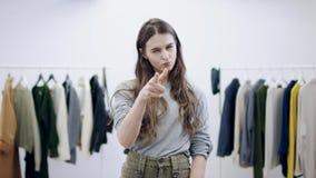 Η νέα γυναίκα με ένα μέσο πρόσωπο δείχνει το δάχτυλό της την οθόνη και παρουσιάζει αντίχειρες κάτω απόθεμα βίντεο