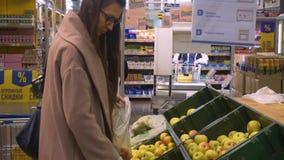 Η νέα γυναίκα με τα ποτήρια και ένα παλτό στην υπεραγορά επιλέγει τα μήλα φιλμ μικρού μήκους