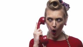 Η νέα γυναίκα στο κόκκινο φόρεμα κάνει τα πρόσωπα κρατώντας ένα τηλέφωνο, σε αργή κίνηση απόθεμα βίντεο