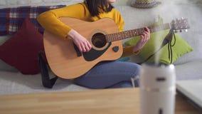 Η νέα γυναίκα συντονίζει την κιθάρα στον πίνακα είναι υπερηχητικός υγραντής απόθεμα βίντεο
