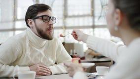 Η νέα γυναίκα ταΐζει το σύζυγό της με μια συνεδρίαση κέικ whle σε έναν καφέ απόθεμα βίντεο