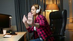 Η νέα ευτυχής γυναίκα στα ακουστικά είναι μουσική ακούσματος και η συνεδρίαση χορού που στην καρέκλα γραφείων, χαλαρώνει μετά από απόθεμα βίντεο