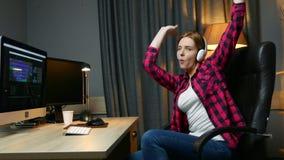 Η νέα ευτυχής γυναίκα στα ακουστικά είναι μουσική ακούσματος και η συνεδρίαση χορού που στην καρέκλα γραφείων, χαλαρώνει μετά από φιλμ μικρού μήκους