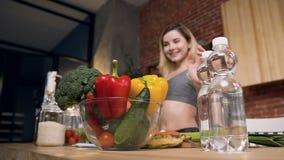 Η νέα και ευτυχής γυναίκα βάζει την κίτρινη πάπρικα στο κύπελλο με τα φρέσκα λαχανικά και τα φρούτα - μπρόκολο, αγγούρι, κόκκινη  απόθεμα βίντεο