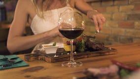 Η νέα κοπή γυναικών έψησε το κρέας με το μαχαίρι και το δίκρανο στη σχάρα ενώ γεύμα στο εστιατόριο σχαρών Γυναίκα που τρώει τη σχ απόθεμα βίντεο