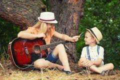 Η νέα μητέρα και το όμορφο υπόλοιπο γιων στο δάσος, τραγουδούν τα τραγούδια κάτω από μια κιθάρα στοκ φωτογραφία με δικαίωμα ελεύθερης χρήσης